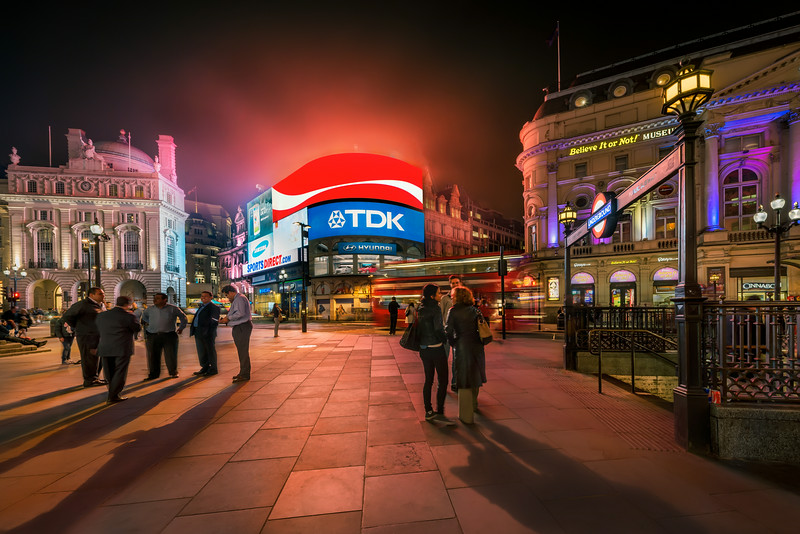 Piccadilly is always crowded - well almost always. And shooting photos there is difficult because of all of the people. But when you patiently are waiting, with your camera on tripod, people also get curious and come talking to you. This particular image is assembled from 9 various photos, with different people and light settings.  Photo by: Jacob Surland, www.caughtinpixels.com